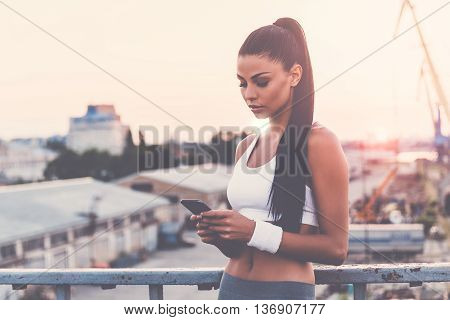 Great day for training. Beautiful young woman in sports clothing holding smart phone and looking at it while standing on the bridge with evening sunlight and urban view in the background