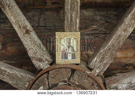 Saint Nicholas icon on vintage wood wheel close up