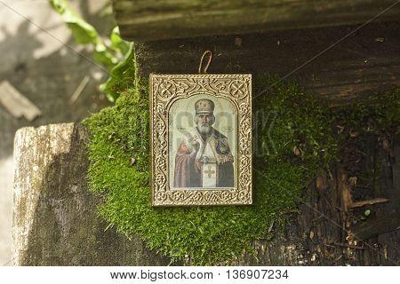 Saint Nicholas icon on green moss close up