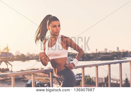 Just keep running. Beautiful young woman in sports clothing running along the bridge and looking over shoulder