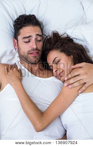 High angle view of irritated man looking at woman relaxing on bed at home