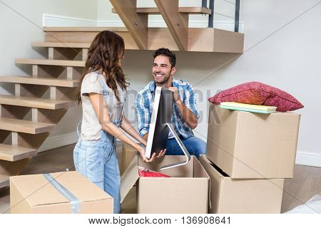 Smiling couple unpacking computer from cardboard box at home