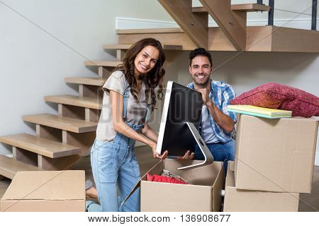 Portrait of happy couple unpacking computer from cardboard box at home