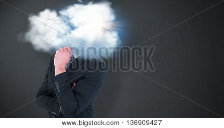 Happy businessman standing with hand on chin against grey background