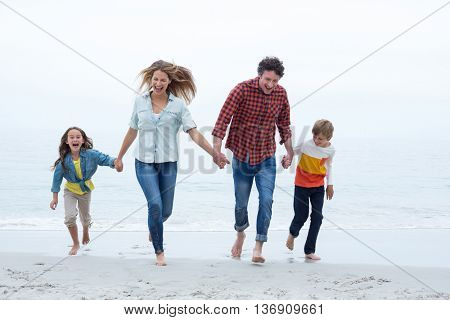 Full length of happy family holding hands while running at sea shore