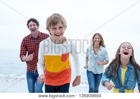 Cheerful family running at beach against sky
