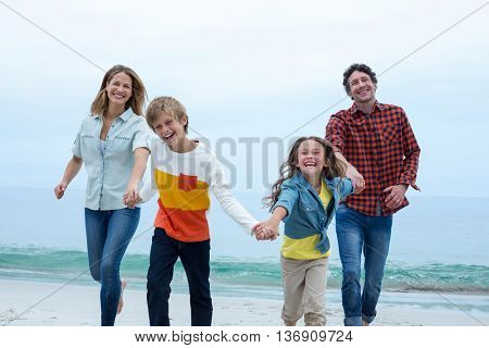 Cheerful family holding hands while running at sea shore