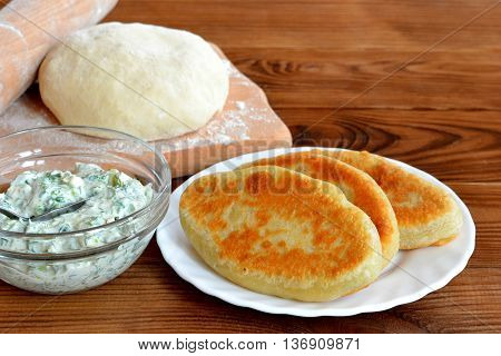 Tasty fried pies on a plate. Dough and rolling pin on a kitchen chopping board. Cheese with fresh dill in a glass bowl. Ingredients for cooking home pies. Wooden background