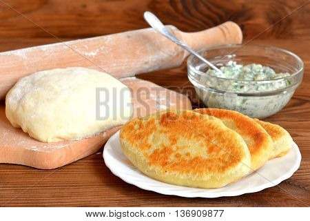 Crispy fried pies on a white plate and on wooden table. Dough and rolling pin on a cutting board. Cottage cheese with green dill in a glass bowl. Home cooking