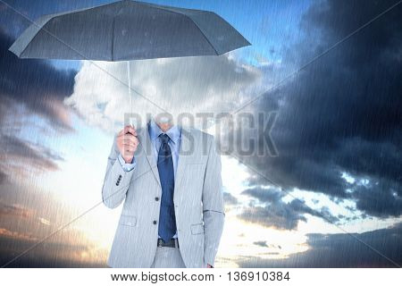 Smiling businessman looking at camera under umbrella against cloudy sky