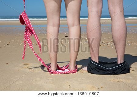 Legs Of Couple At The Sea With Bikini Down And Hat