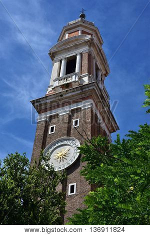 Church of the Holy Apostles of Christ baroque bell tower with clock built between 17th and 18th century rise above trees