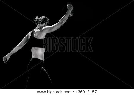 Side view of sporty woman preparing her discus throw against black background