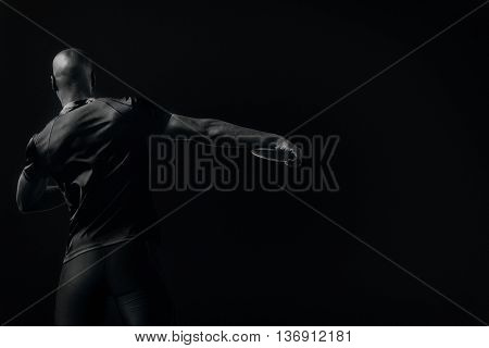Rear view of discus pitcher against black background