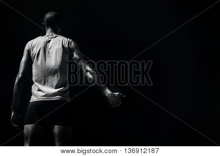 Rear view of sportsman holding a discus on a white background against black background