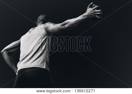 Low angle view of sportsman is practising discus throw against black background