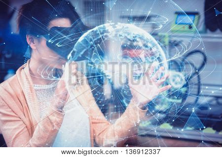 Global technology background in blue against female graphic designer using the virtual reality headset