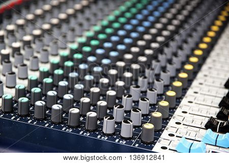 Part of a professional sound mixing console music device for audio signals with controlling knobs and slider
