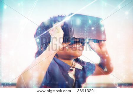 Glowing blue background against elementary girl looking through virtual reality headset in school library