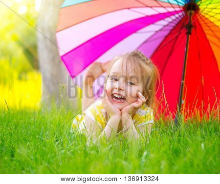 Portrait of a smiling little girl lying on green grass under the colorful umbrella. Cute child enjoying nature outdoors. Healthy carefree kid playing outside in summer park. Suntan protection