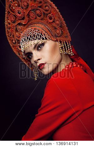 Woman posing in red dress and metal headwear on balck background
