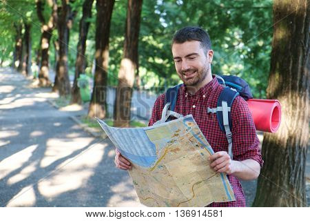 Man tourist with a map exploring outdoors