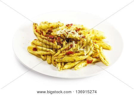 homemade pasta variety called capunti with garlic and oil pickled tomatoes and parmesan cheese specialty from southern Italy on a plate isolated with shadow against a white background selective focus