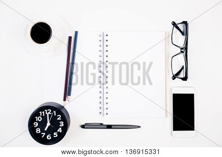 Top view of bright office table with blank spiral notepad other stationery items coffee cup glasses clock and blank cellular phone. Mock up