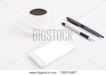 Closeup of bright office desktop with blank white smart phone coffee cup and two pens. Mock up