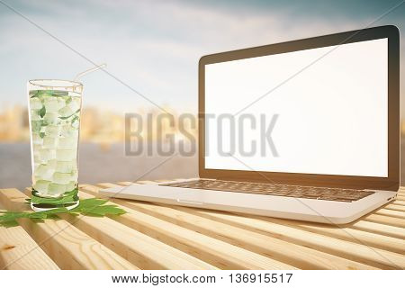 Closeup of laptop with blank white screen and mojito cocktail on wooden planks. Blurry sea and city view in the background. Mock up 3D Rendering