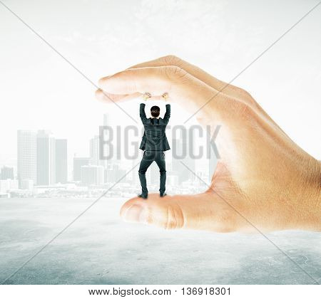 Businessman trapped between fingers of big hand on abstract city background. Pressure concept