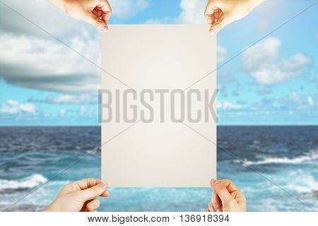 Four hands holding blank poster on sea and sky background. Mock up