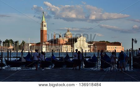 VENICE, ITALY - JUNE 17: Saint George Basilica at sunset with tourists and gondola JUNE 17, 2016 in Venice, Italy