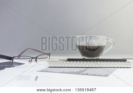 Closeup black coffee in cup of coffee on note book and pencil with work paper on blurred wooden desk and glass wall textured background work concept by coffee work paper and eyeglasses in art tone