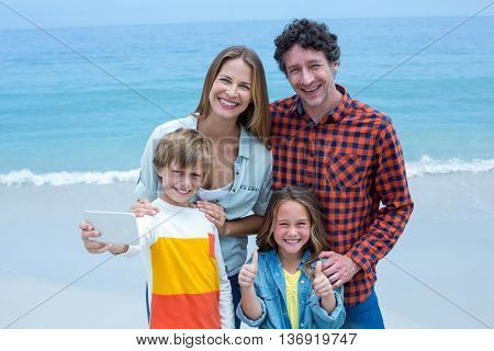 Portrait of cheerful family taking selfie while standing at sea shore