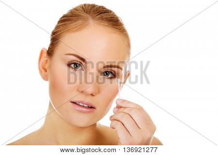 Young woman removing eye makeup with cotton swab