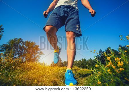athlete running through the meadow. Feet, bottom view