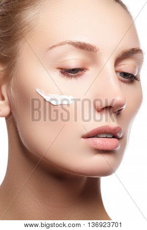 Beautiful Young Woman With Cosmetic Cream On A Cheek