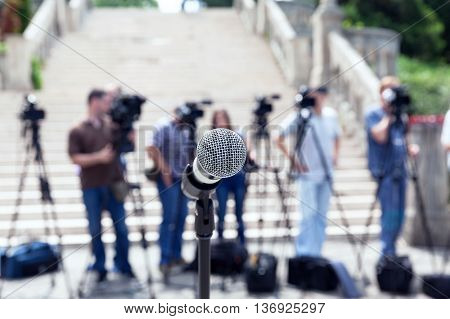 Microphone in focus against blurred camera operators and reporters. News conference.
