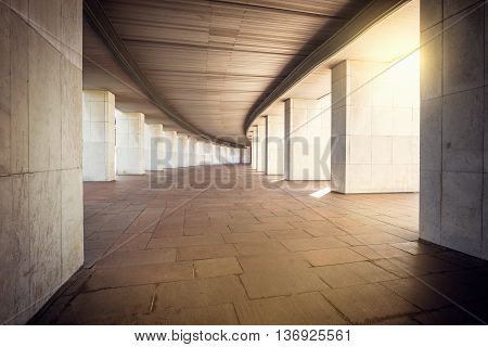 Long wide corridor of the building with columns at evening time.