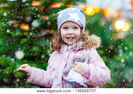 Cute little smiling kid girl with christmas tree. Happy child in winter clothes and toy choosing xmas tree on Christmas market with lights on background. Family, tradition, celebration concept
