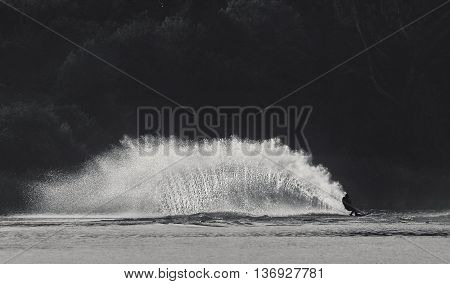 Man going on water slides in calm evening, Black and white photo. Vintage style photo. Water sport. Man. A young caucasian man wake boarding on lake