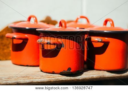Cooking pots with lids orange enamel old outdoor on sunny day on wooden background