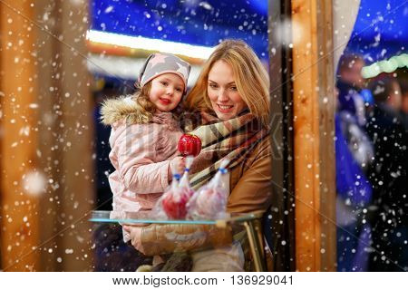Beatiful woman and little kid girl eating crystalized sugared apple on German Christmas market. Happy family in winter clothes with lights on background. Family, tradition, holiday concept