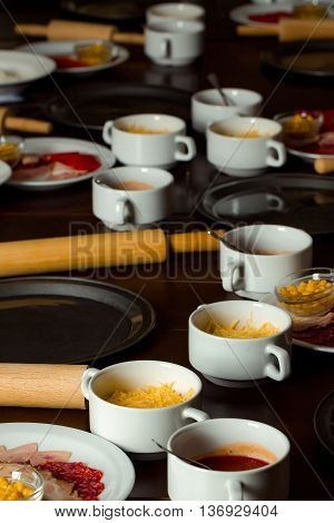 Ingredients for cooking pizza cheese tomato sauce in portion cups sliced ham sausages with trays and rolling pins on kitchen table on wooden background