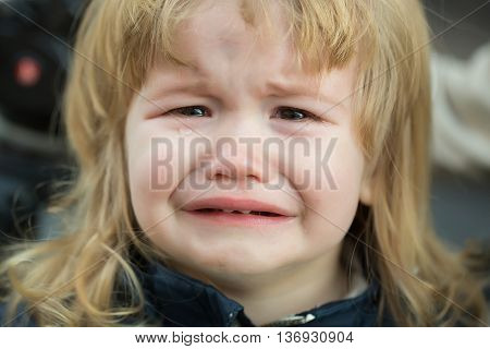 Little boy with cute emotional face and blond long hair cries with tears outdoor