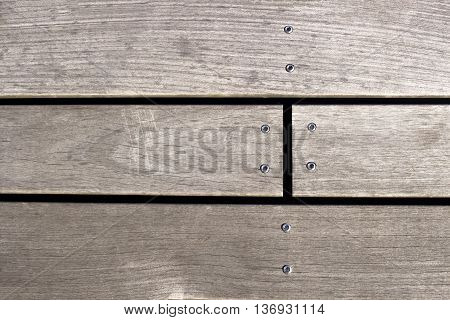 Closeup of a screw screwed into wooden plank.