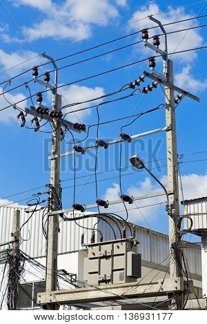 The High voltage electrical transformer is installed on the platform of a high concrete pole and high power of electric voltage cable the danger area. vertical image