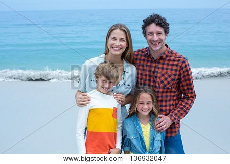 Portrait of cheerful parents with children standing on shore at beach