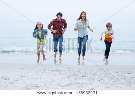 Full length of cheerful family running at beach against sky